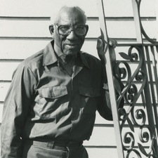 Philip Simmons standing next to a gate, ca. 1995, Philip Simmons Collection, courtesy of the Avery Research Center.
